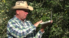 Farmer sending by email using notebook test results from olive tree plantation. Stock Footage