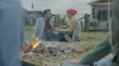 4K Happy friends sitting around a bonfire on the beach, young couple talking Arkistovideo