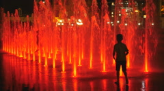 Children run through coloured fountains at night. Quebec City. Stock Footage