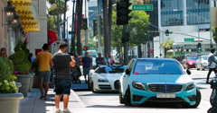 Tourist take pictures of luxury cars near Beverly Wilshire Hotel in Los Angeles Stock Footage