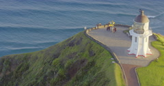 Aerial over hills looking out the to Cape Reinga Lighthouse, New Zealand Stock Footage