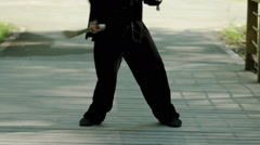 Man practicing elements of tai chi. A man rotating steel swords around a body HD Stock Footage