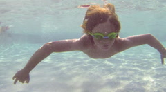 Happy child diving in a swimming pool Stock Footage