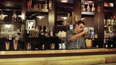 Young man working as a bartender in a nightclub bar Stock Footage