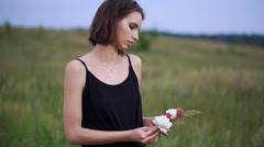 Beautiful slender girl creates a wreath of flowers Stock Footage