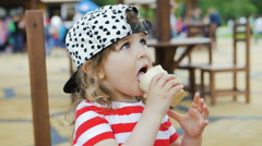 Little girl sits on the chair and eats ice cream Stock Footage