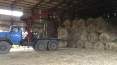 Unloading rolls of hay Stock Footage