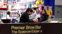 People having threading tint waxing at Premier brown bar - stock footage