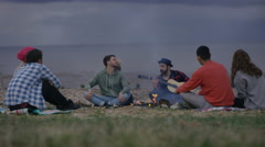 4K Happy friends sitting around a bonfire on the beach, playing guitar & singing Stock Footage