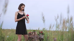 Beautiful slender girl creates a wreath of flowers Stock Footage