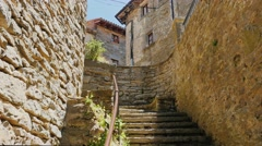 Woman tourist climbs the steps of the ancient town in Catalonia - Rupit. Popular Stock Footage