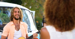 Woman taking a picture of a man playing guitar Stock Footage