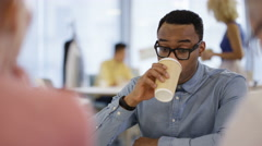 4K Portrait smiling young professional drinking coffee in office breakout area Stock Footage