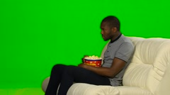Man with dark skin watching TV and eating popcorn. Green screen Stock Footage