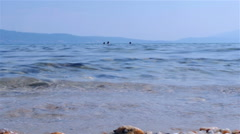 Close up of wavy sea, swimmers in the blurred background by Sheyno, low angle. Stock Footage