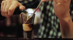 Bartender pouring and mixing three different liquids, a cocktail, close up Stock Footage