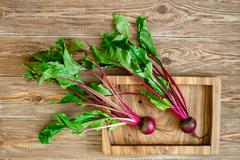 Beet with a tops of vegetable and on wooden tray Stock Photos