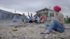 4K Friends with bonfire at the beach, portrait of young woman smiling to camera Arkistovideo