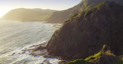 Aerial flying over rocky coastline and ocean at Cape Reinga, New Zealand Stock Footage