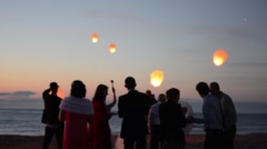 Sky lantern flying in night sky. Happy people celebrating wedding on the beach. Stock Footage