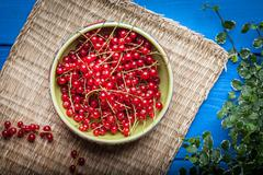 Redcurrant in wooden bowl. - stock photo