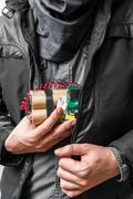 Terrorism concept. Terrorist has dynamite bomb in jacket. - stock photo