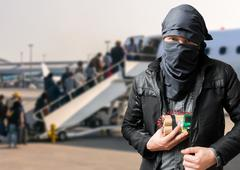 Terrorist has dynamite bomb in jacket in airport. Terrorism concept. Stock Photos