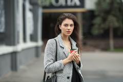 Lifestyle fashion portrait of beautiful young brunette woman in grey coat Stock Photos
