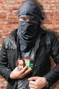 Terrorist puts dynamite bomb in jacket. Terrorism concept. Stock Photos