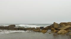 Sandy beach with choppy rough sea, yellow rocks, dense gray clouds covering sky. - stock footage
