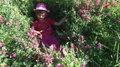 The girl child is playing in the tall grass in the meadow. Stock Footage
