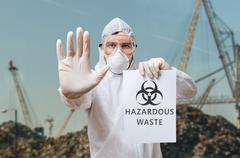 Technician in coverall warns in landfill about hazardous waste. Stock Photos