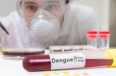 Scientist in overall is analyzing blood sample in test tube for Dengue fever. Stock Photos