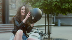 Brunette female in leather jacket, taking off motorcycle helmet, then laughs Stock Footage