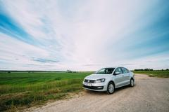 Volkswagen Polo Car Parking On A Roadside Of Country Road On A Background Stock Photos