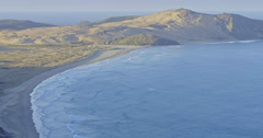 Aerial over hills out to the ocean and beach at Cape Reinga, New Zealand Stock Footage