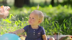 Little girl one year old has fun with a balloon on a green meadow Stock Footage