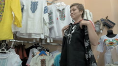 A customer trying to find perfect blouse in store Stock Footage