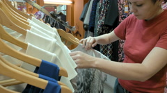 A female customer is browsing through the cloths - stock footage