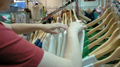 A female customer is browsing through the cloths Stock Footage