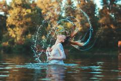 Women's hair makes water spray. Stock Photos