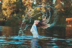 Woman emerged with a splash of water. Stock Photos