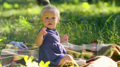 Little girl one year old enjoys soap bubbles on a green meadow on a sunny day Stock Footage