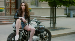 4K CINEMAGRAPH - Beautiful girl in leather jacket sitting on motorcycle Stock Footage