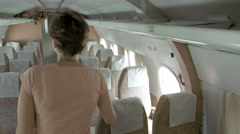 A passenger is walking in the aisle of a plane Stock Footage