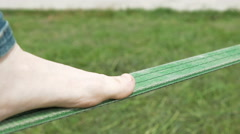 A person is balance walking on a green rope Stock Footage