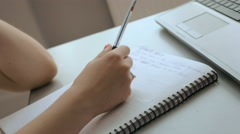 Female types and takes notes in notebook Stock Footage