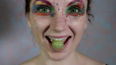 4k Shot of a Woman with Multicoloured Make-up Eating Gooseberry Stock Footage