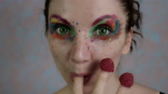 4k Shot of a Woman with Multicoloured Make-up Eating Raspberry Stock Footage