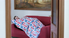 Funny man on sofa while put the blanket on him Stock Footage